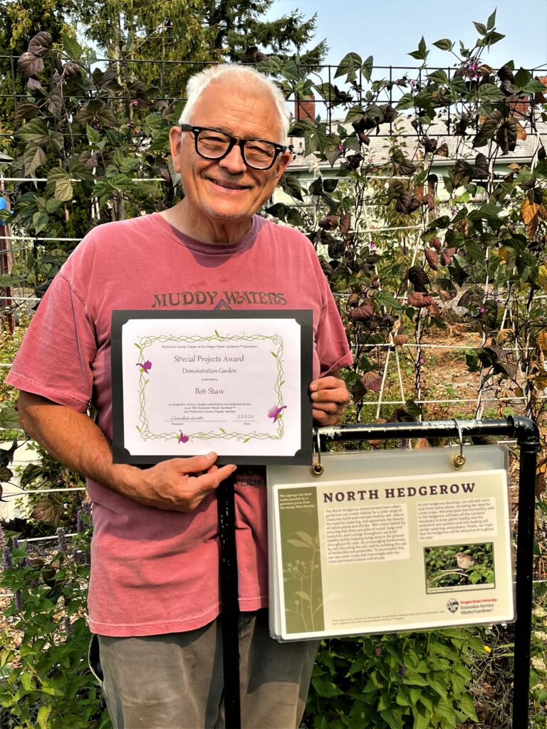 Man holding certificate, in a garden.