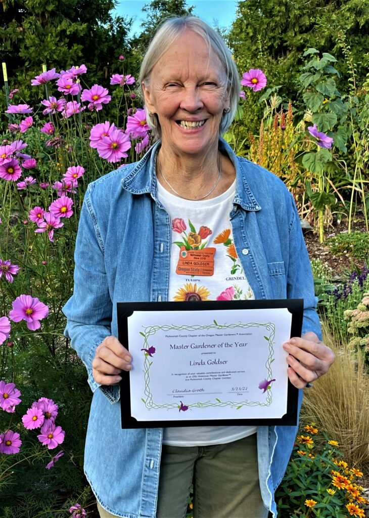Woman holding a certificate in a garden with blooming cosmos flowers in the background.