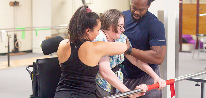 two kinesiology student helping a women engage in adapted physical therapy