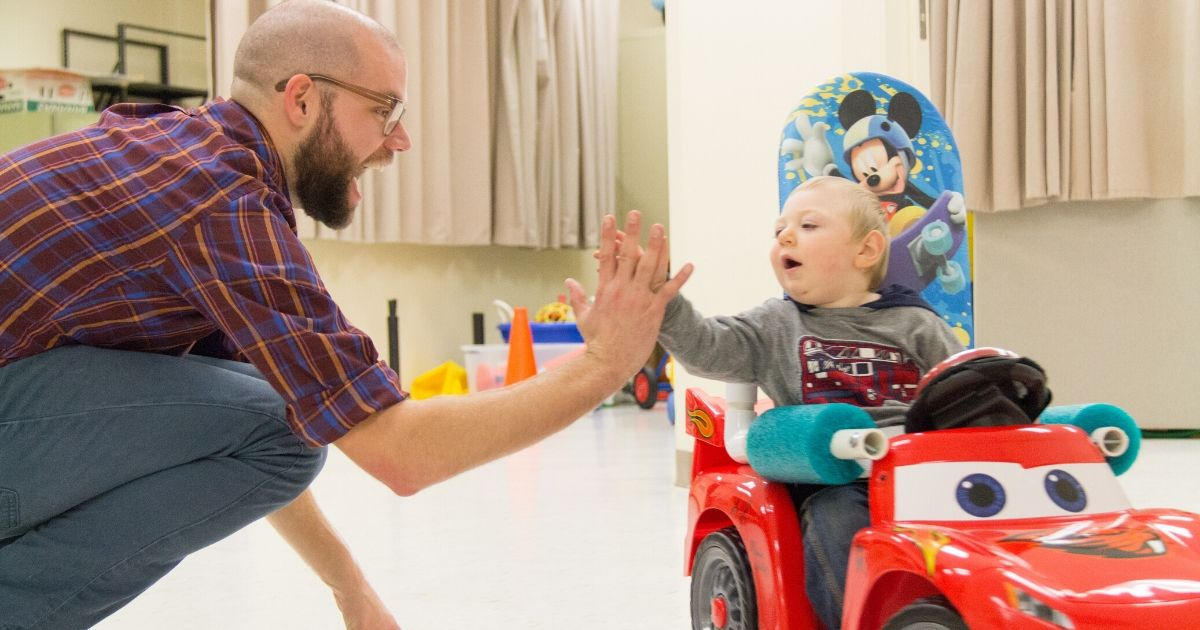 Researcher Sam Logan high-fives a child in a Go Baby Go car