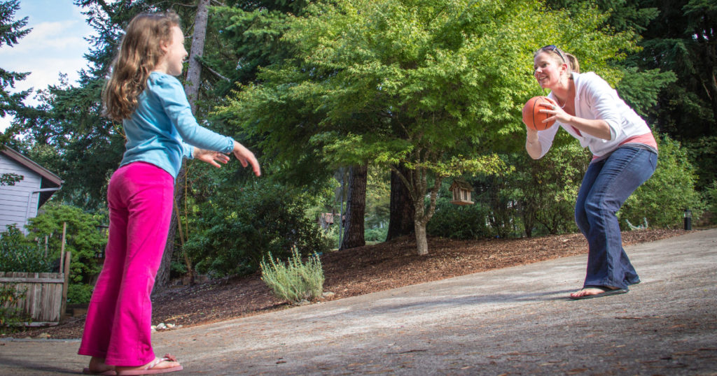child playing a game with a basketball with adult