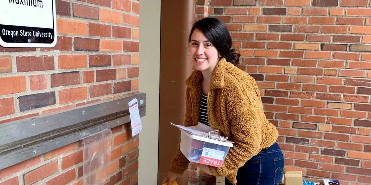 Female student in an orange jacket picking up a COVID test kit