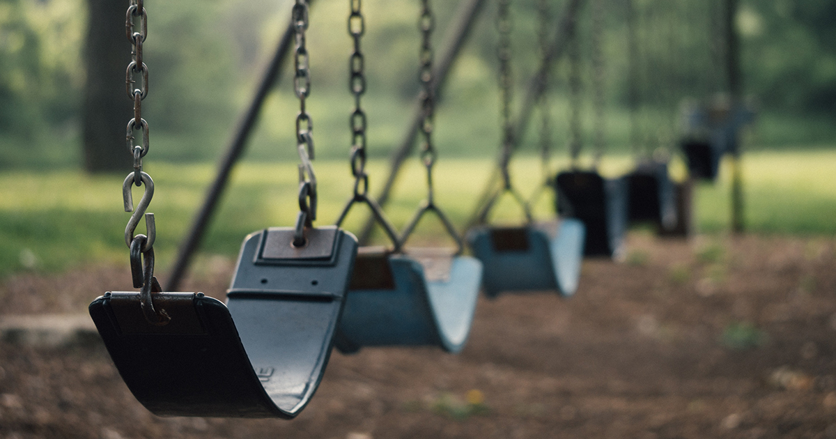 close up of swings in empty playground
