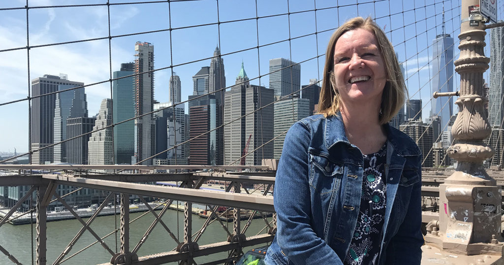 woman poses in front of city skyline