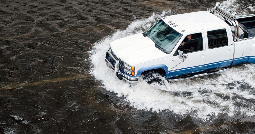 white and blue truck driving in flooded street