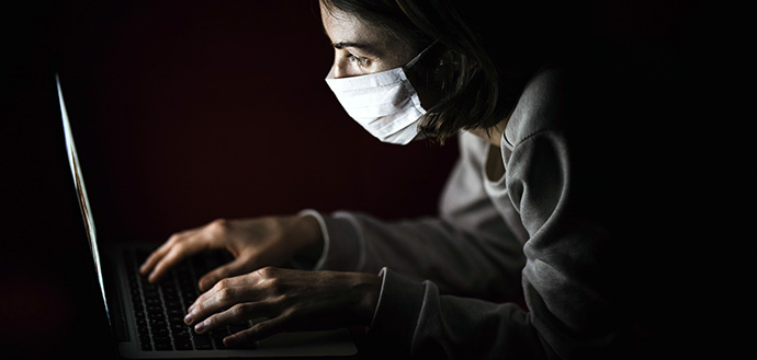 woman in face mask uses a laptop