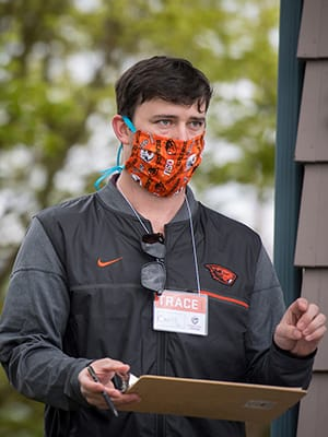 worker holds TRACE clipboard while wearing beaver face mask