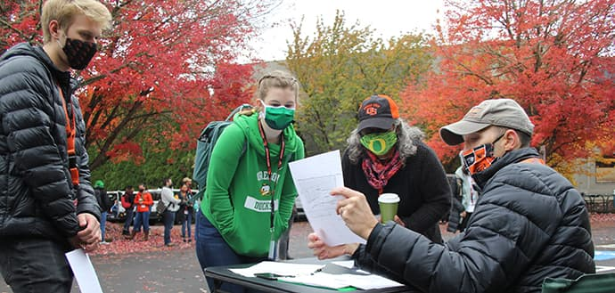OSU and UO students wearing masks going over TRACE-COVID-19 project duties with project leader Jeff Bethel