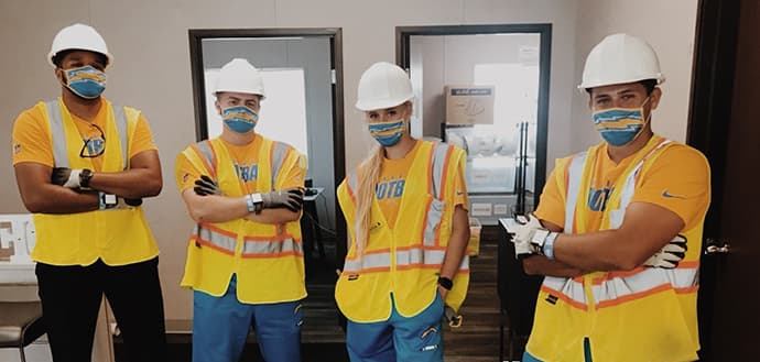 group of NFL athletic training interns wearing hard hats and masks