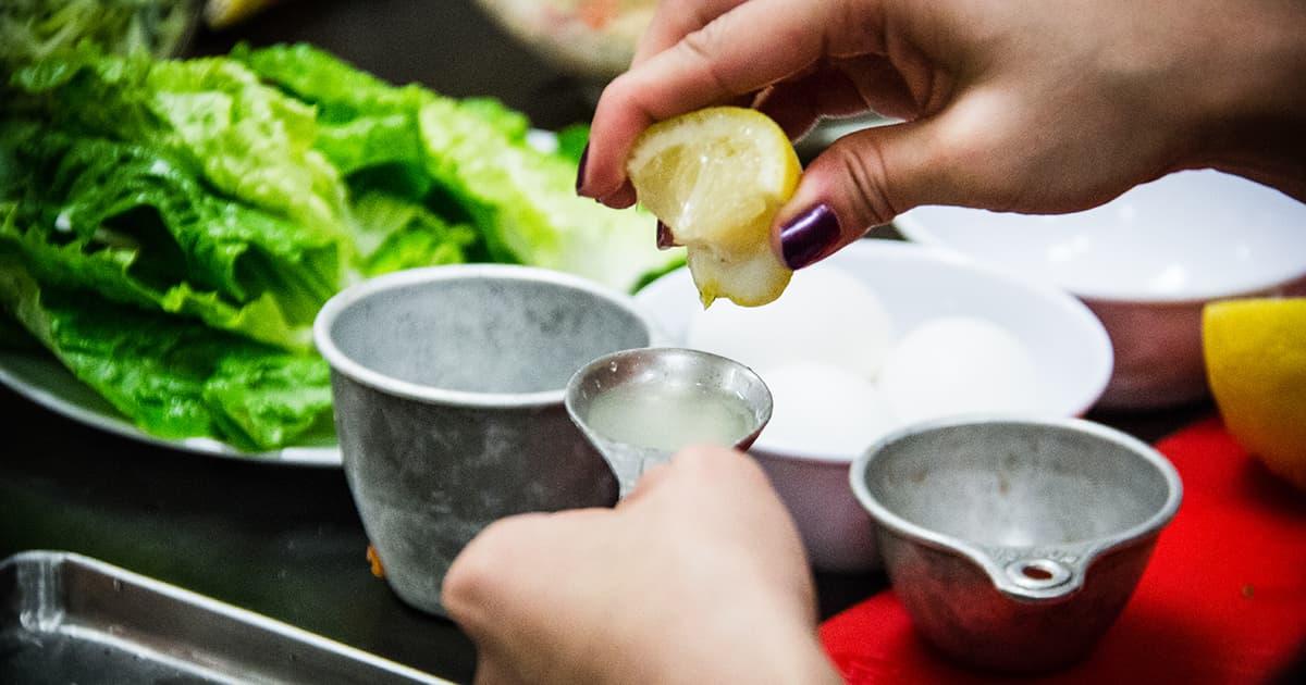 hands squeeze lemon juice into measuring spoon