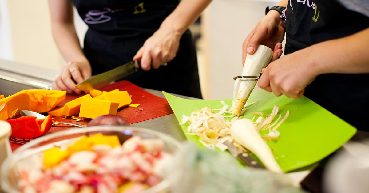 two students chopping and peeling vegetables