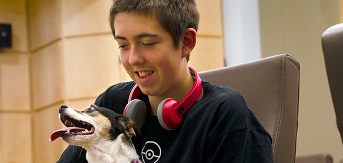 young boy sits with dog in lap, headphones around his neck and smiling, dog has his tongue out