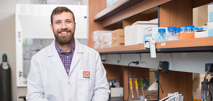 Harrison Stierwalt smiles in Oregon State lab coat, laboratory