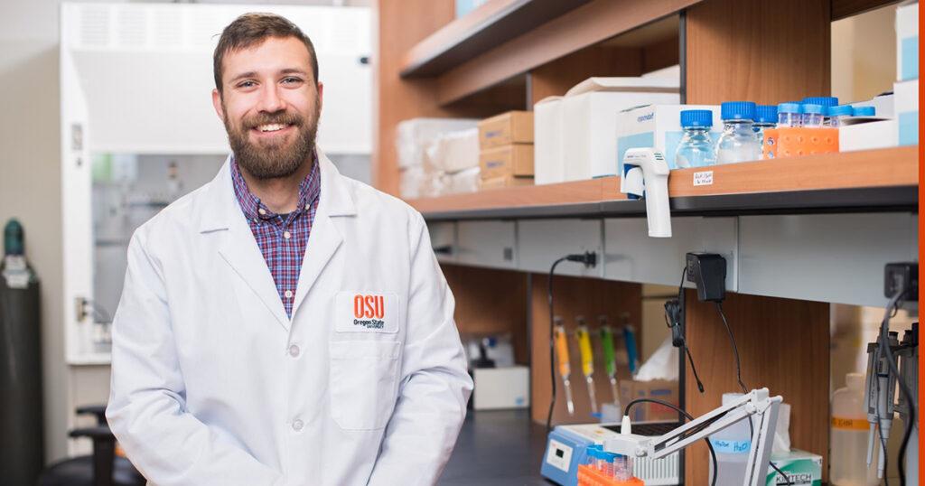 Harrison Stierwalt smiles in Oregon State lab coat, laboratory