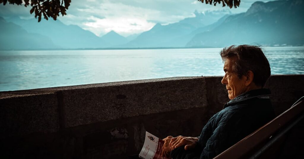 elderly man looks out at lake, mountains