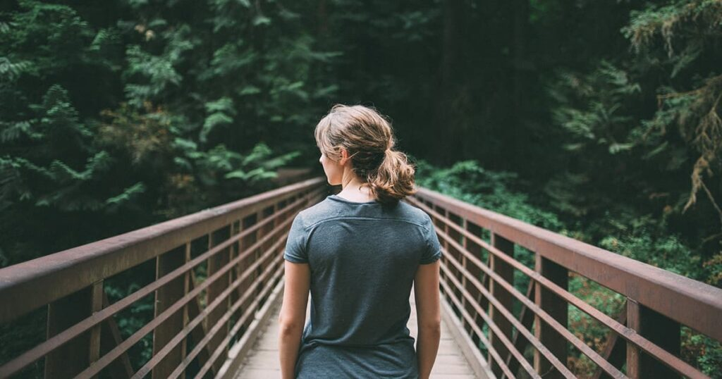 blonde woman stands on bridge, looks at forest