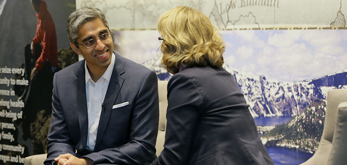 Vivek H. Murthy, MD smiles while sitting and talking to a woman