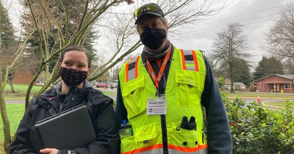 Two OSU Extension volunteers pose for photo in face masks, outdoors