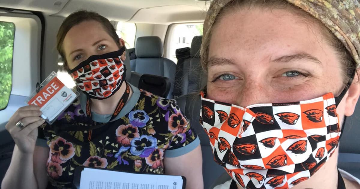 two females wear Oregon State University face masks, hold up TRACE name tags