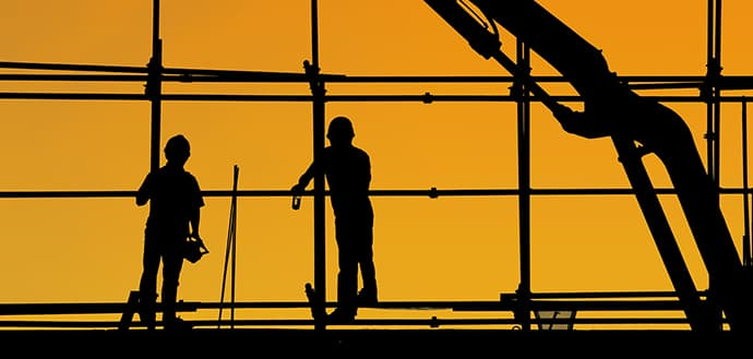 Two silhouetted construction workers with orange background