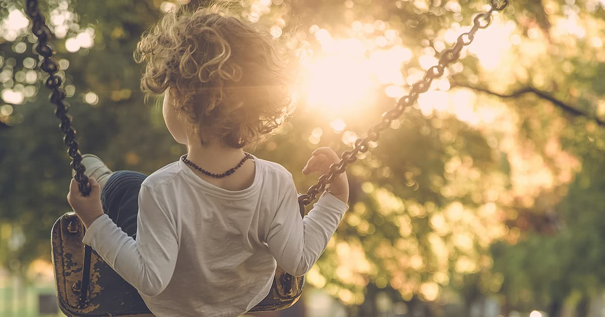 young blonde child sits on a swing with back to camera, sunlight shines through trees