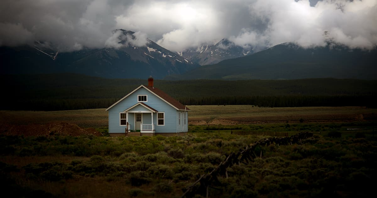 blue house in a field with nearby mountains