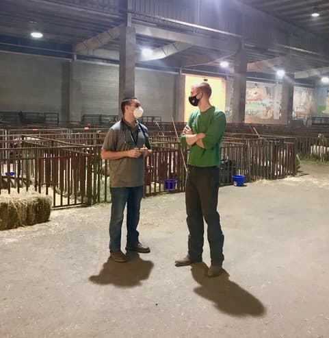 Ryan Scholz talking with colleague, wearing masks