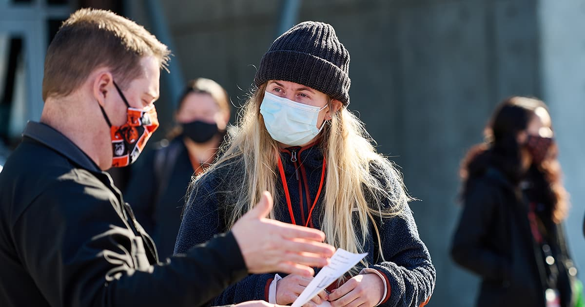 Female wearing mask listens to male wearing a mask and reading off paper