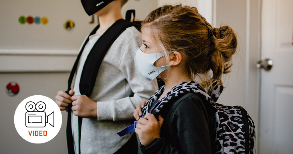 young girl with backpack and face mask