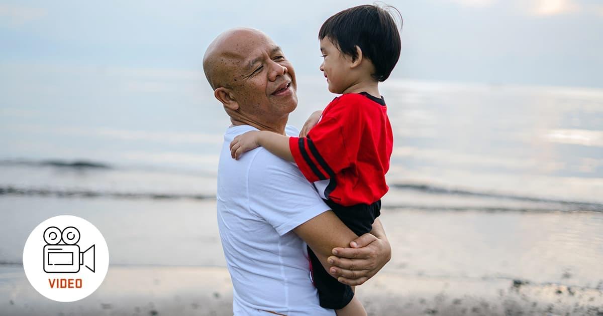 grandparent holds toddler on the beach