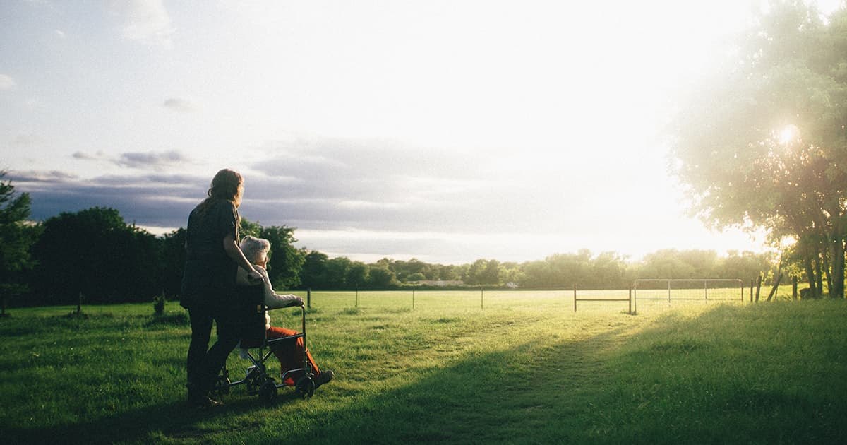 Woman pushes grandma who is in wheelchair out in a field at sunset
