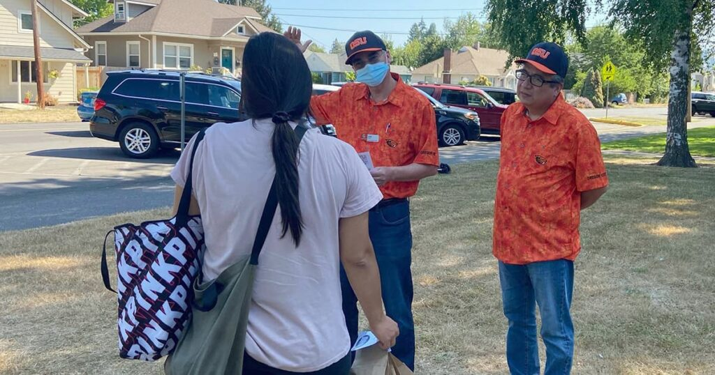 Jamie and Rafael speak to a young Latino woman about the local vaccine clinic happening in Newberg, Oregon
