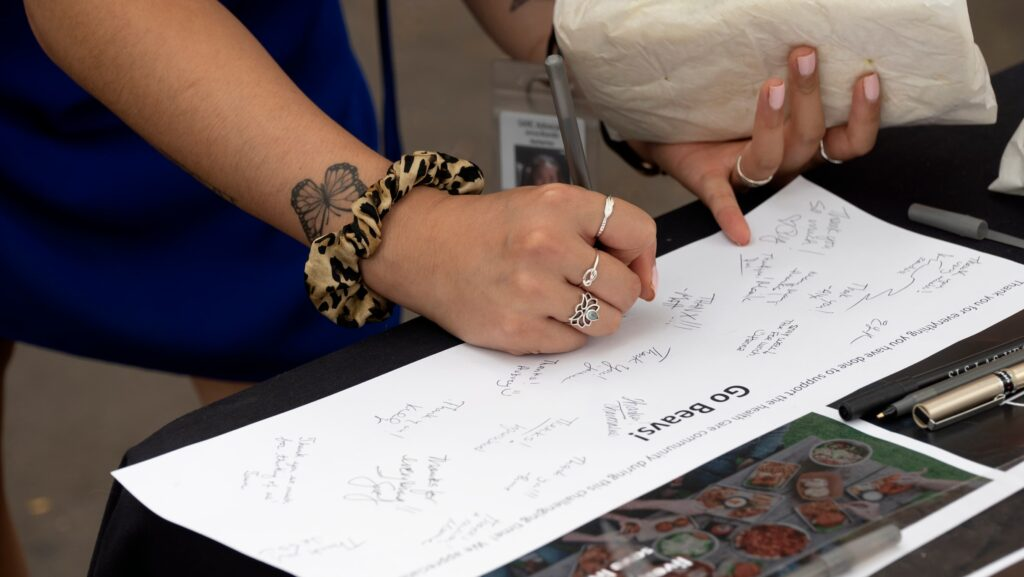 Women wearing rings signs a thank you poster for Selfless Servings team