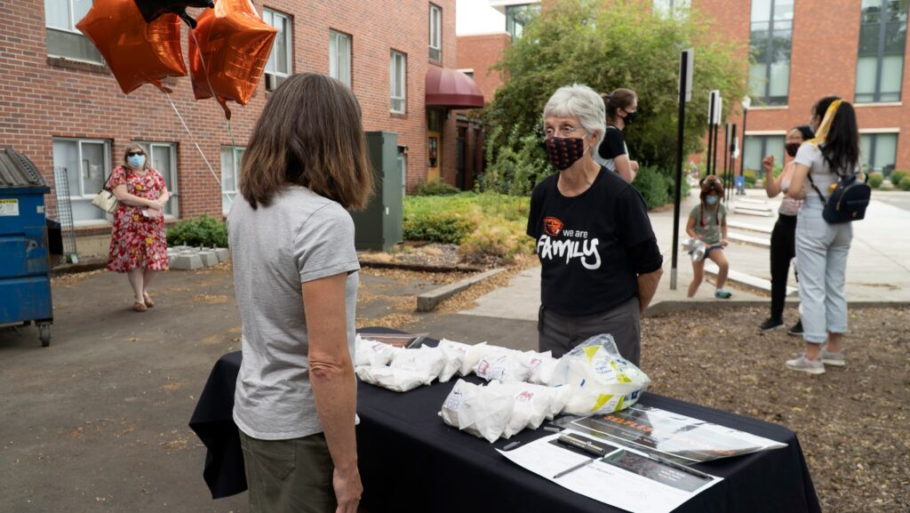 A volunteer speaks with a health care worker about food options in front of her