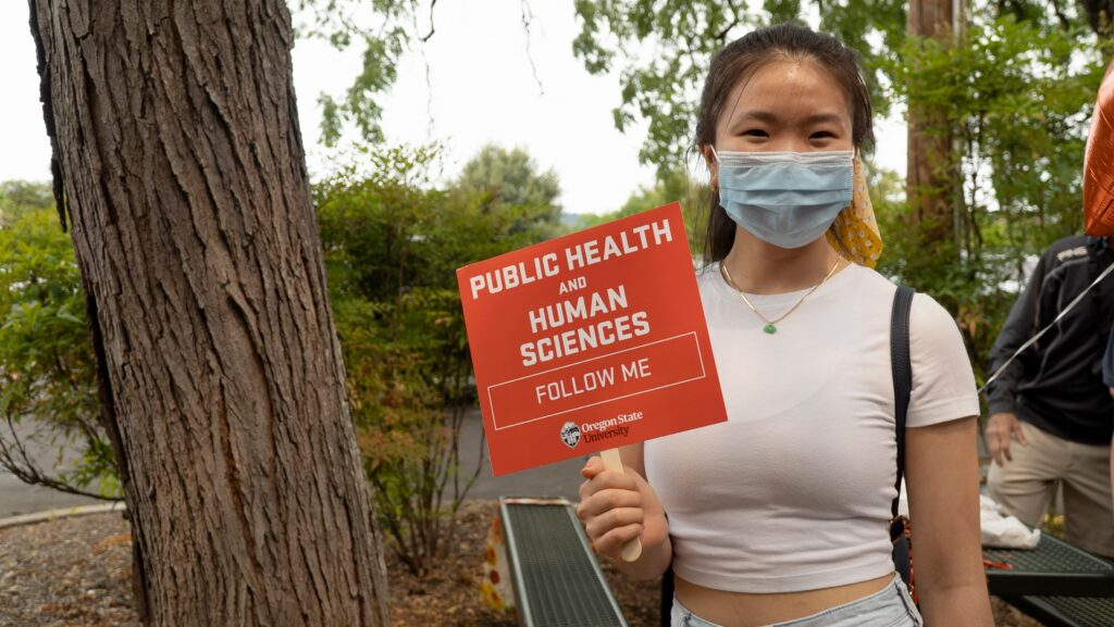 Amanda Tran holds a College of Public Health and Human Sciences sign