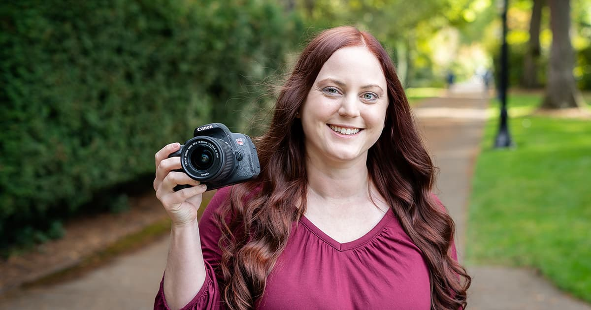 Alexis Croisdale holds up a DSLR camera and smiles
