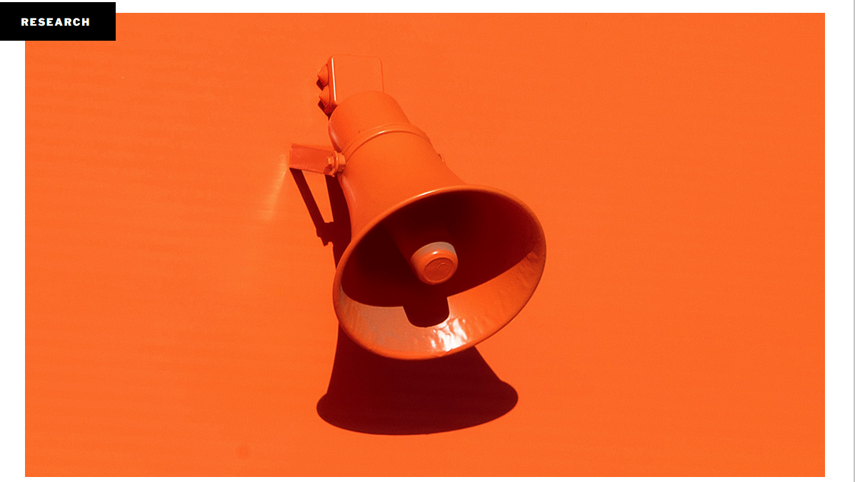 Picture of an orange wall with an orange speaker shaped like a megaphone attached to it