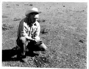 Grant County Extension ag and 4-H agent Bill Farrell examining soil at a Grant County ranch.