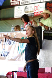 Carrie Harris takes bids during the 2020 Coos Youth Livestock Auction.