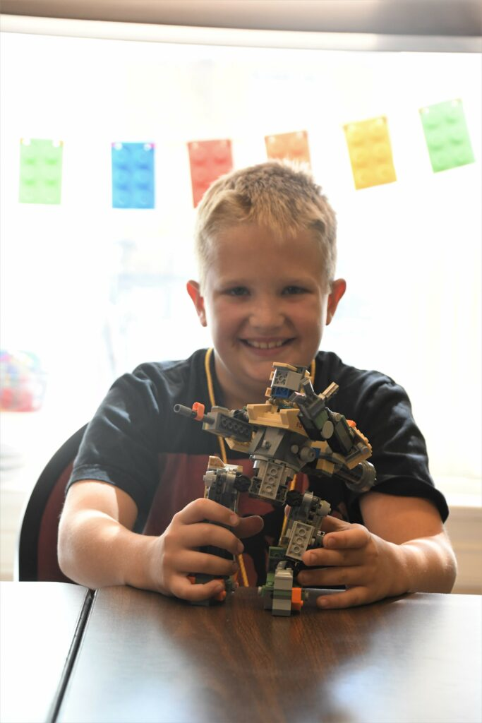 A young boy holding a small LEGO robot he made at 4-h camp.