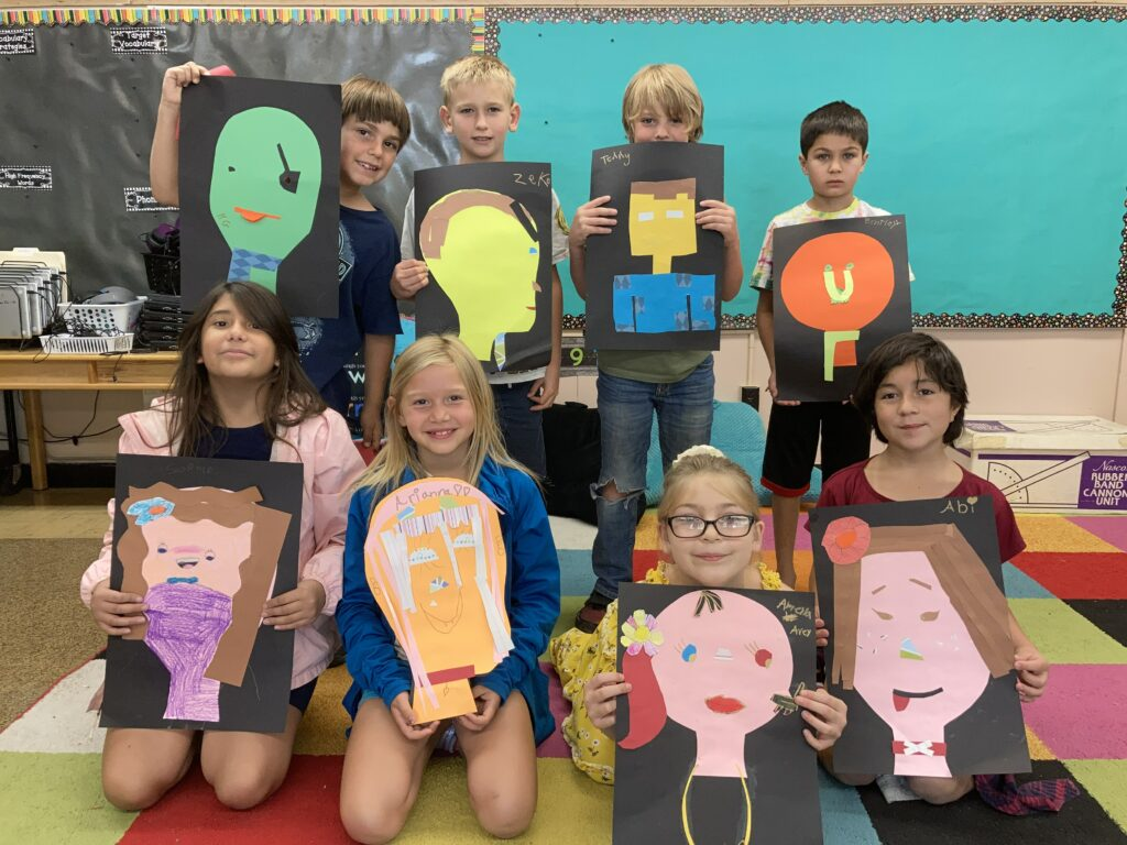 A class of 2nd grade youth at Fremont Elementary summer school holding their self-portraits made from construction paper.