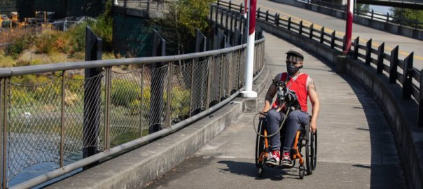 Dorian is traveling down a sidewalk in his wheelchair on a sunny day with a small dog in his lap.