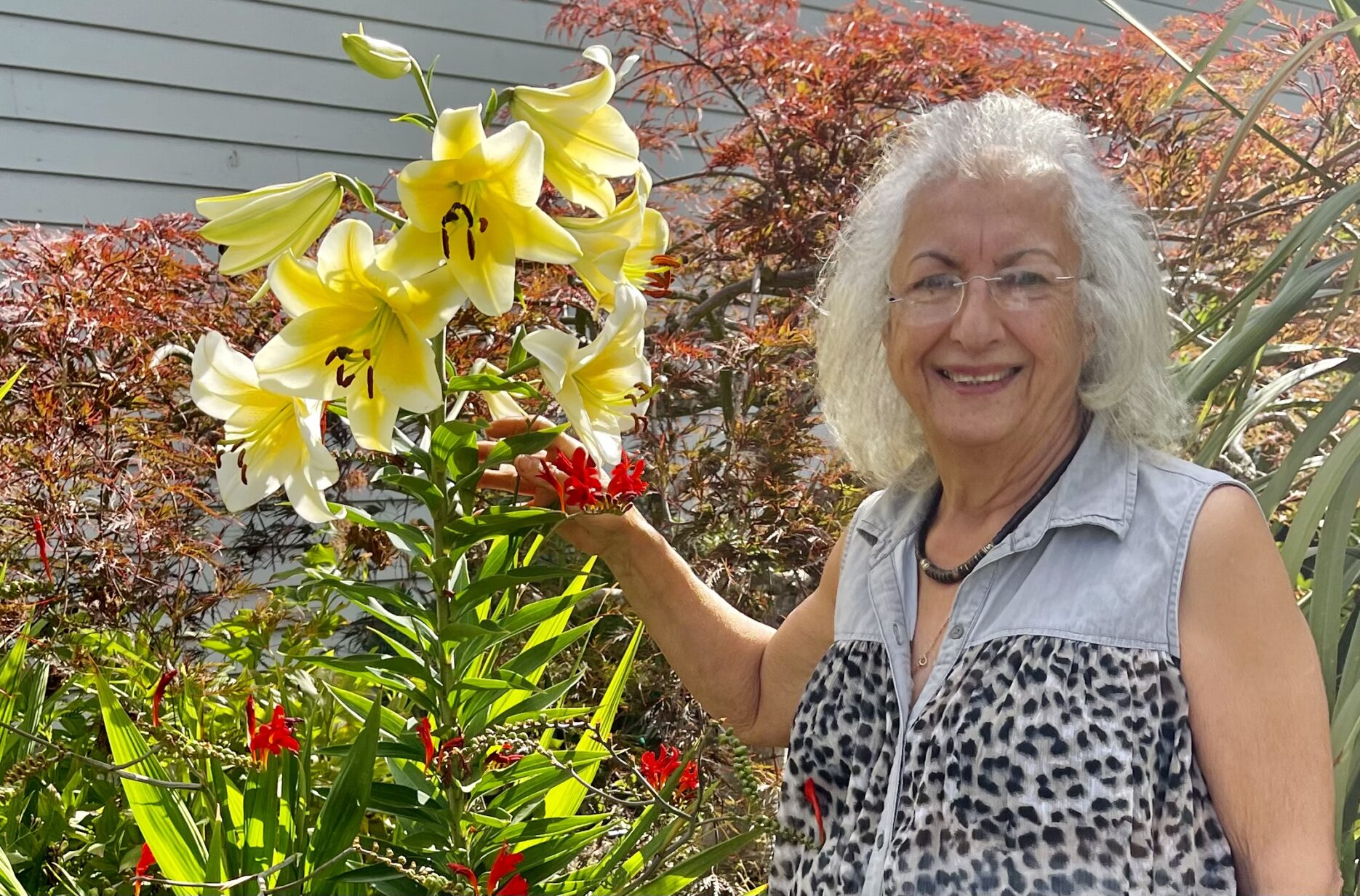 farah in her garden with tall yellow flower