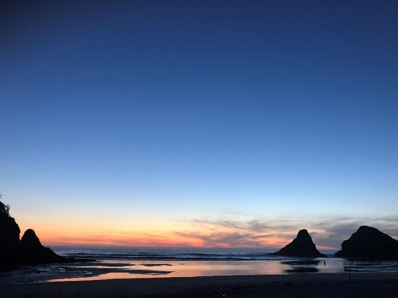 View of the sunset over the ocean. Heceta Head sea stacks in the foreground.