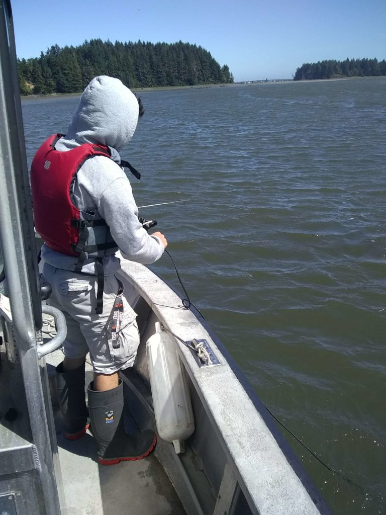 Student researcher Lucas Parvin stands on a boat lowering monitoring equipment into the water of the South Slough.