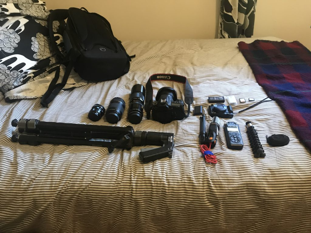 Video equipment laid out on a bed.